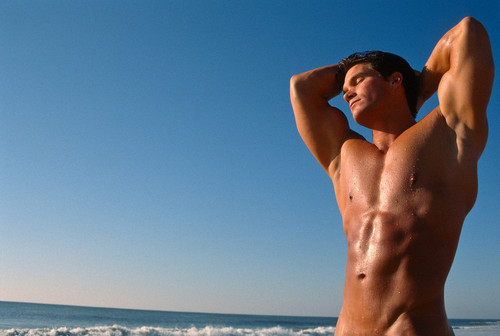 muscular-tan-man-enjoying-the-beach-and-sun_large